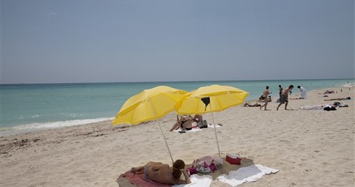 In this Wednesday, May 9, 2012 photo, a sun bather lies under umbrellas on Miami Beach, Fla. In a study released Thursday, May 10, 2012, the Centers for Disease Control and Prevention says half of adults under 30 say they've had a sunburn at least once in the past year. Experts worry it's a sign young people aren't paying much attention to warnings about skin cancer, including the deadliest kind. (AP Photo/J Pat Carter)