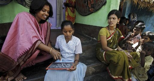 Indian woman Arati Devi, left, who conducts free school for illiterate women helps a girl write on a slate in Dhunkapada village in Ganjam district, Orissa state, India, Monday, Sept. 8, 2014. While India has a growing middle class, tens of millions of women still struggle with illiteracy, poverty and little social status. Monday marked International Literacy Day. (AP Photo/Biswaranjan Rout)
